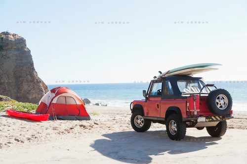 an SUV parked near a tent and Kayak on the beach